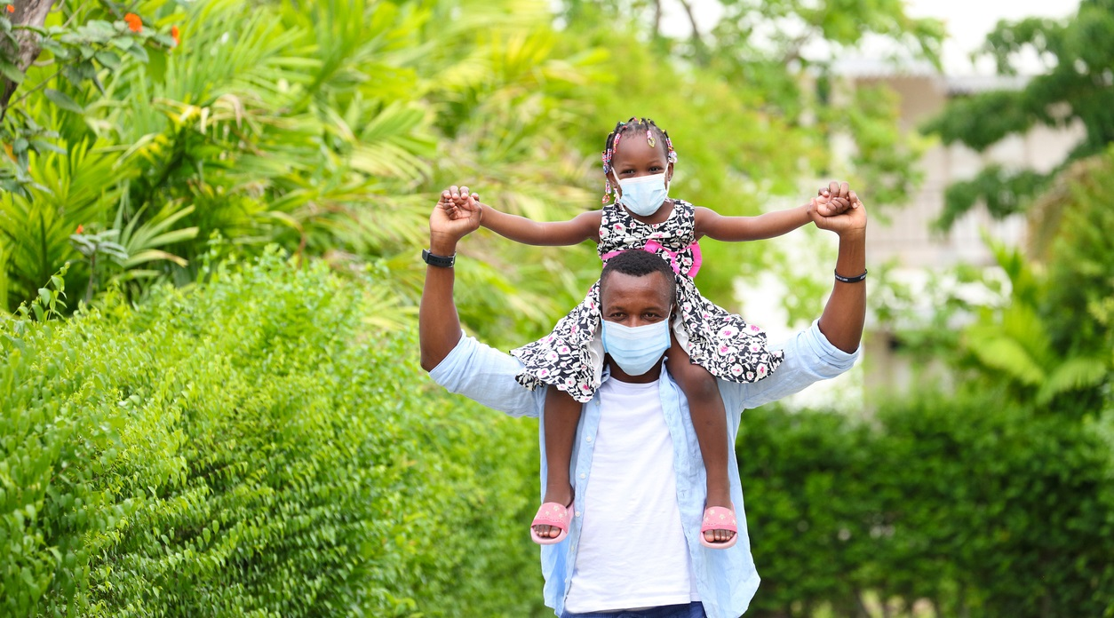 Black man in mask carrying masked child on shoulders