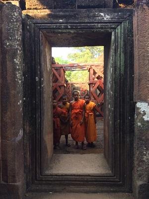 boys in buddhist robes standing in doorway