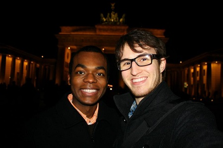 Black man and White man in front of gate