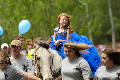 young girl with red hair and blue dress rides white horse, Anna Leigh