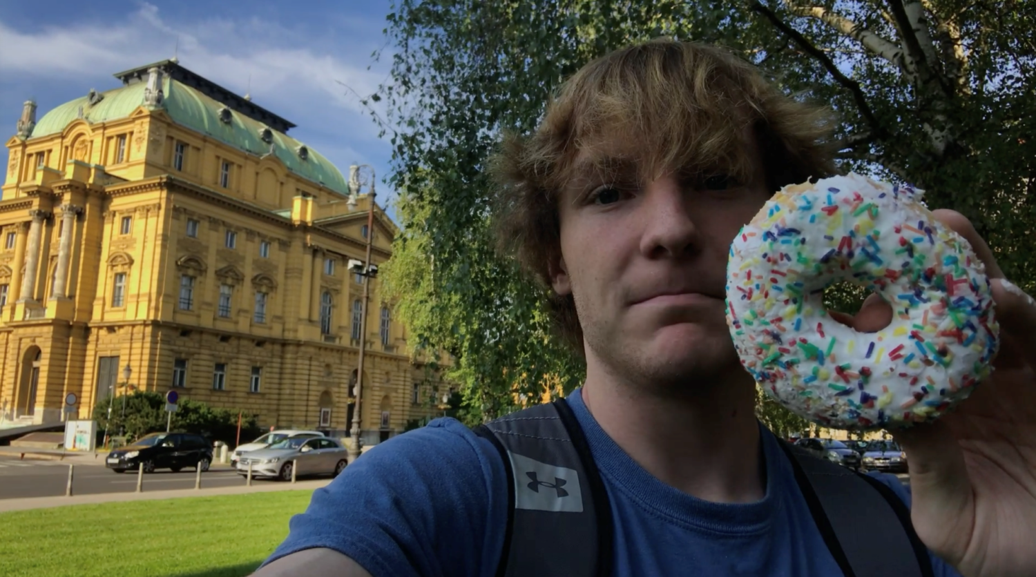 white male in blue T-shirt holding doughnut, Charlie Lott '21