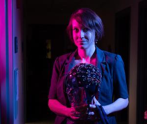 woman in dark room holding an electrode cap, Erin Wamsley