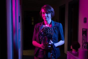 woman in dark room holding electrode cap, Erin Wamsley