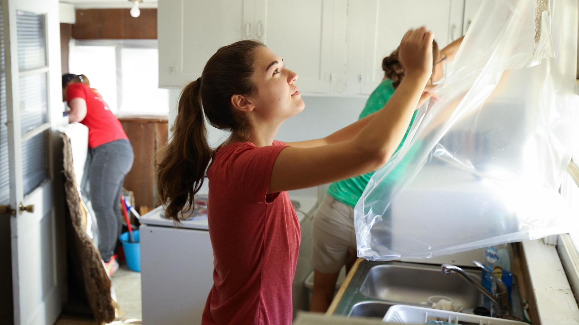 Volunteers with Furman's Community Conservation Corps work on weatherizing a home.