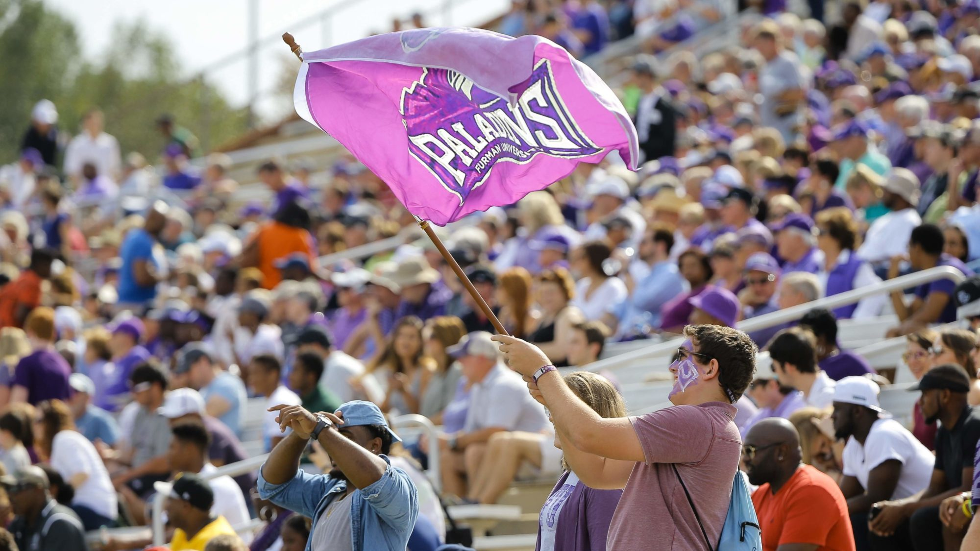 A fan waves a large Furman Paladins flag in front of a large crowd.