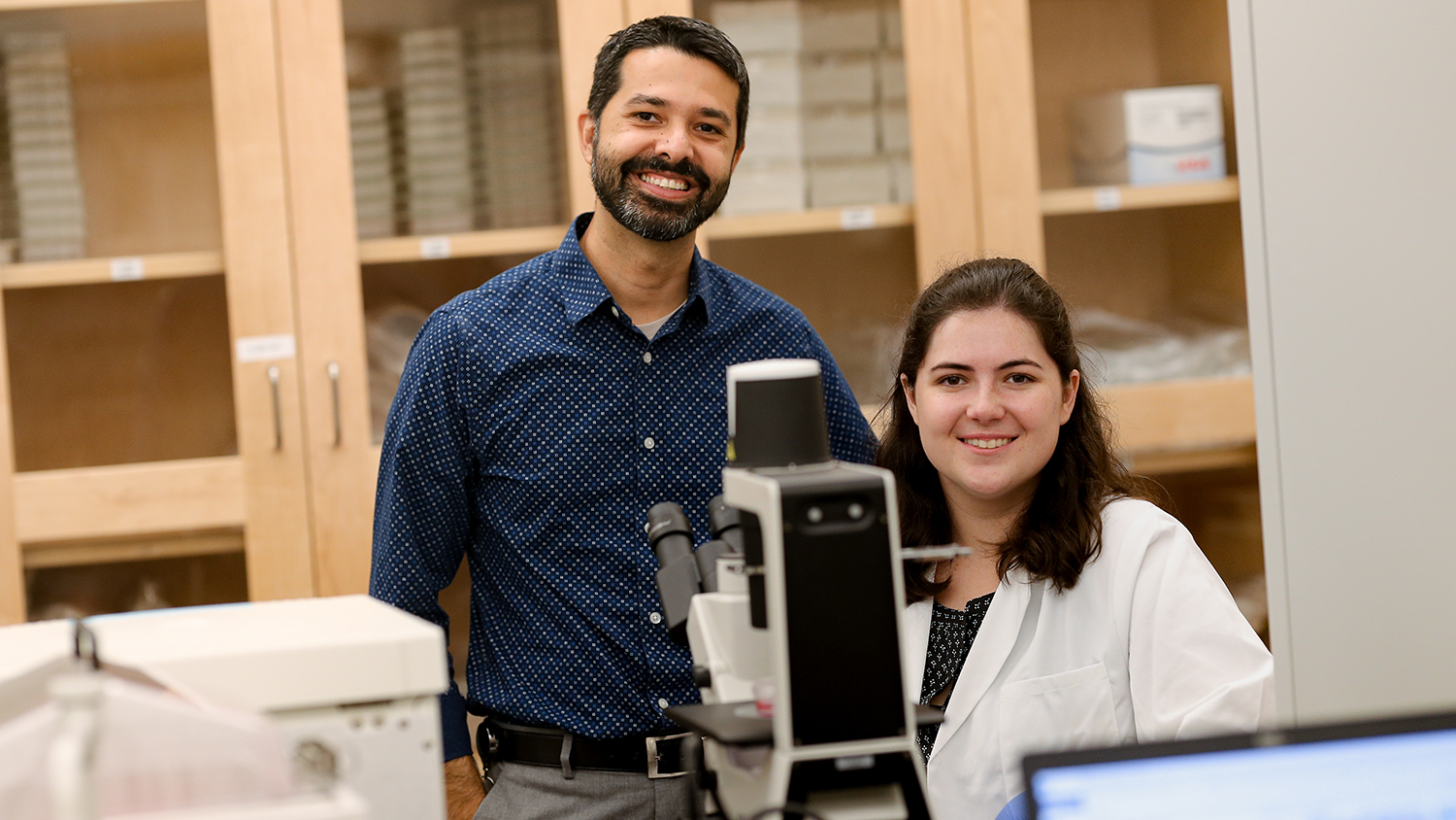 A male professor and a female student at a microscope in a lab.