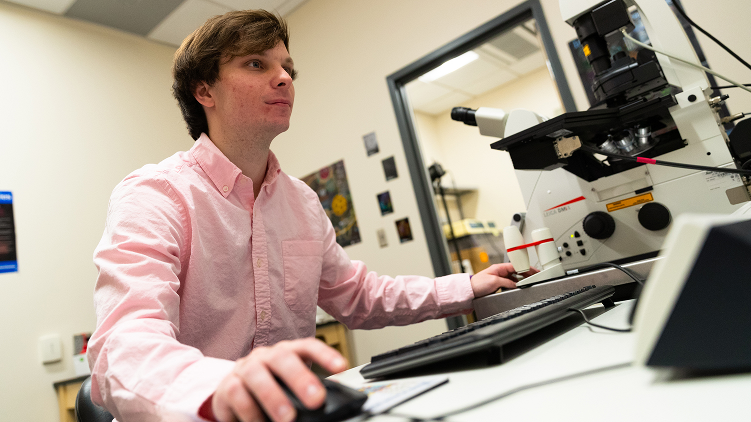 A young man sits at a microscope in a lab.