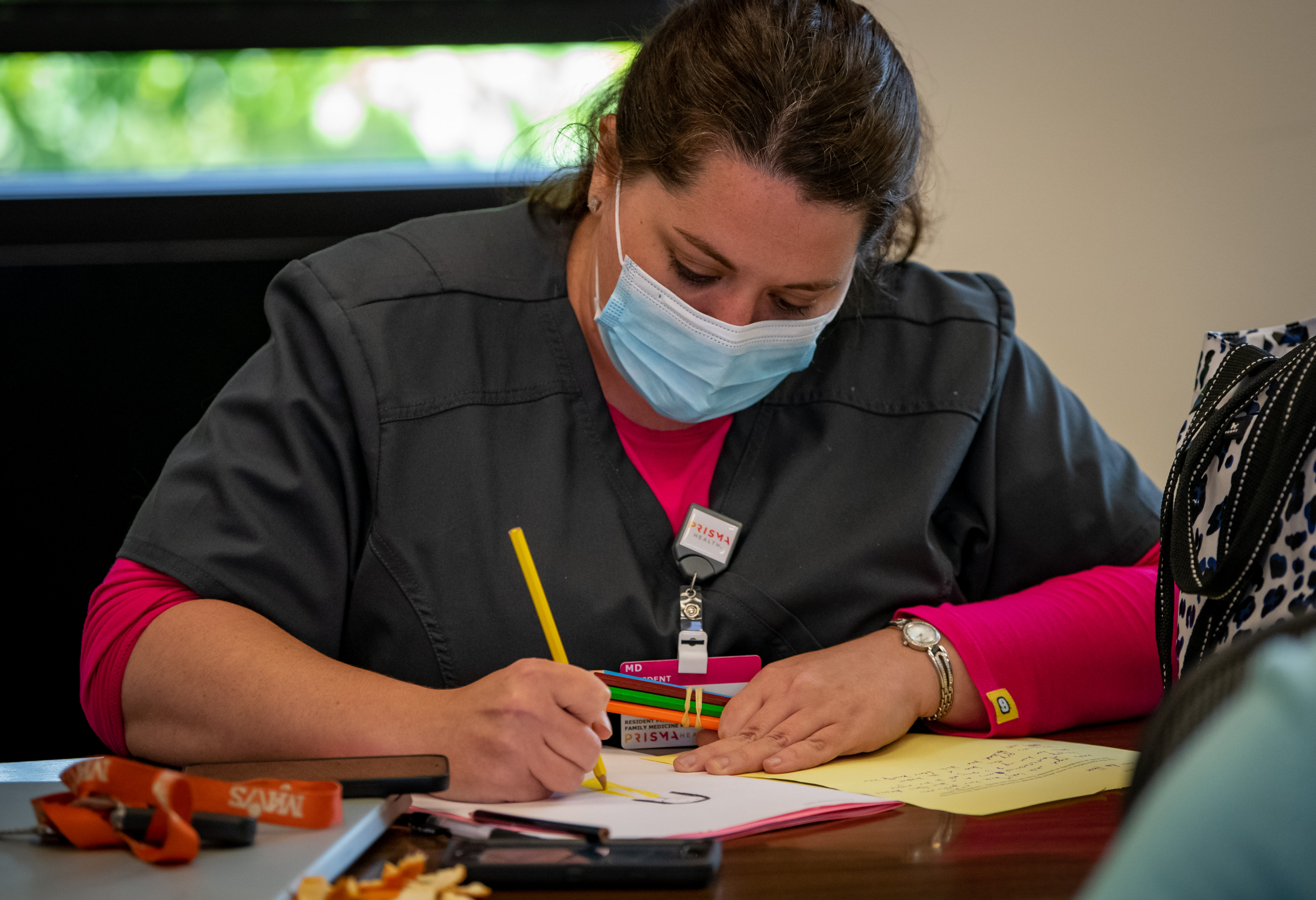 A woman in scrubs and a mask draws with colored pencils.