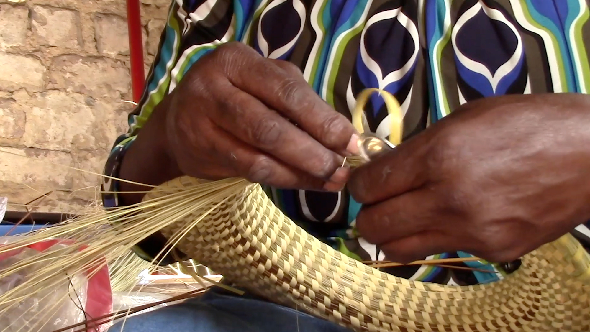 """An artisan weaves a basket in a scene from """"The History of Sweetgrass Baskets,"""" a documentary by Alexis Hildenbrandt '22."""