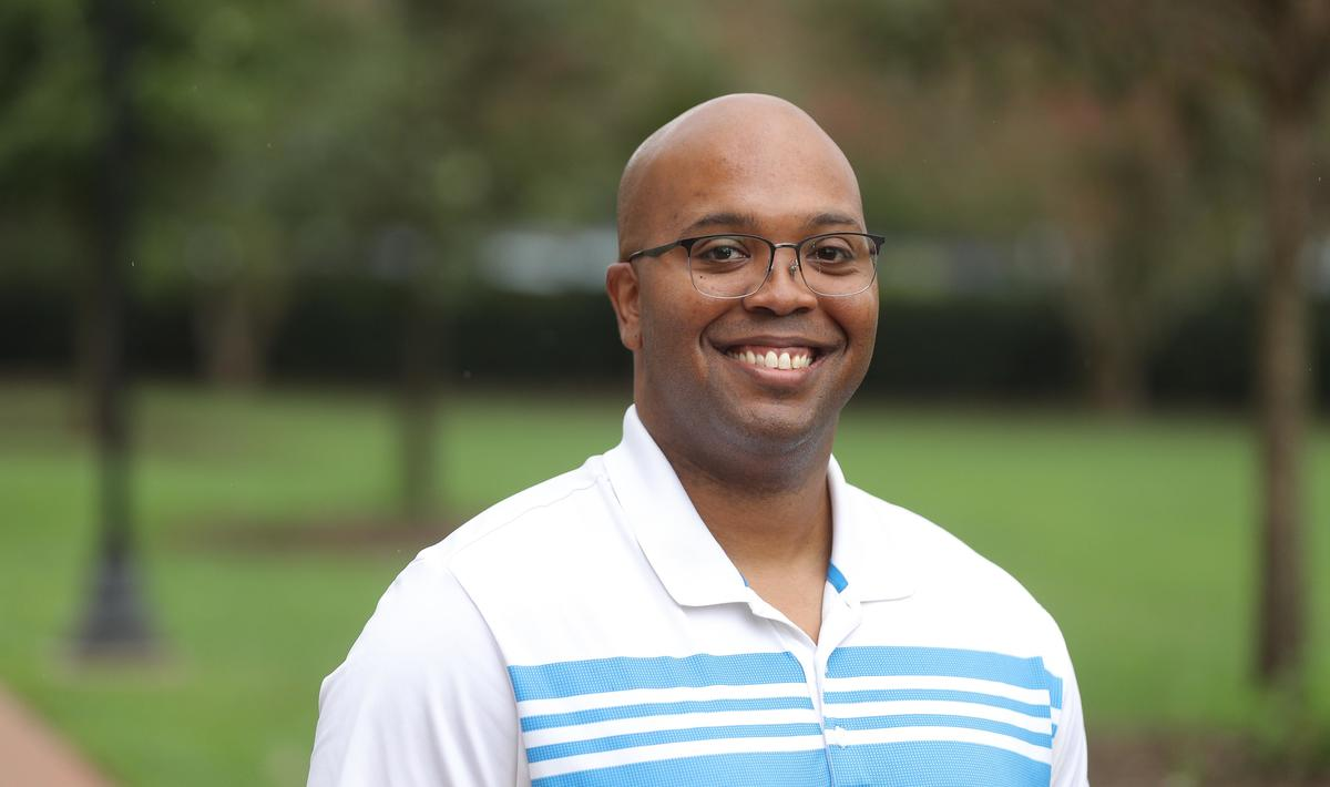Black man in glasses, white and blue striped shirt, Holly Pinheiro