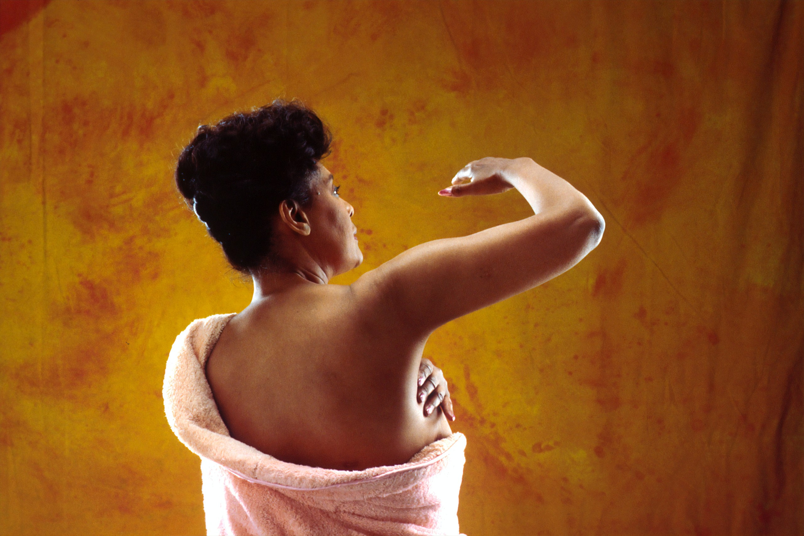 Rear-facing woman completes a breast self-examination