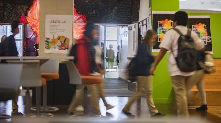 students walking across bright hallway