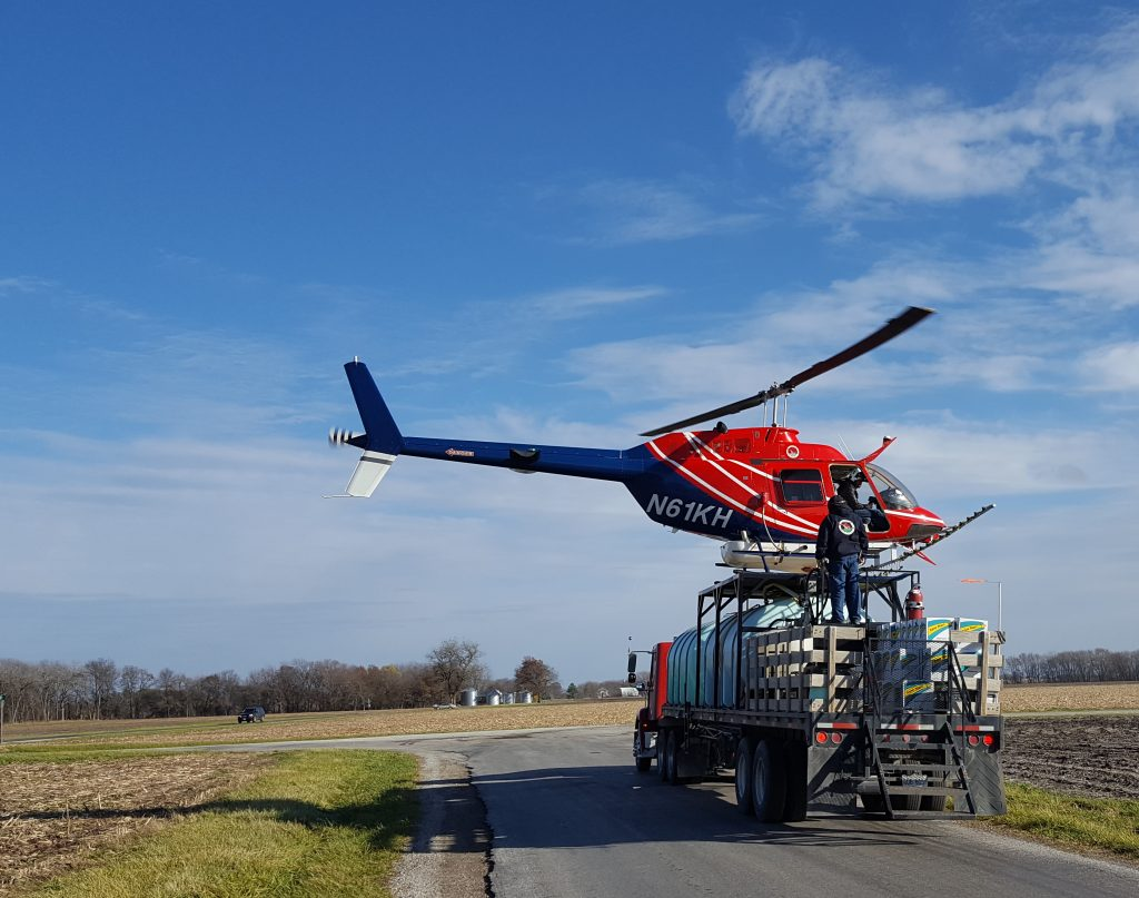 A helicopter sits atop a semi-trailer on a rural road with agricultural fields surrounding the road. A woodland is in the far background.