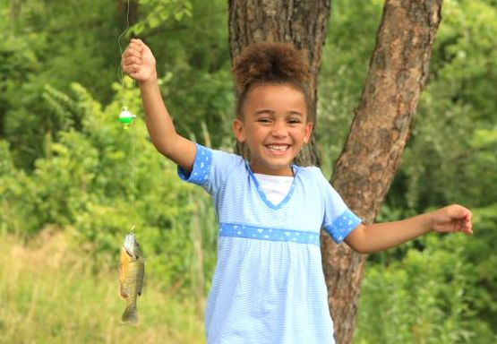 A young girl holds up a fishing line with a small blue-gill fish hooked on line. She is smiling.
