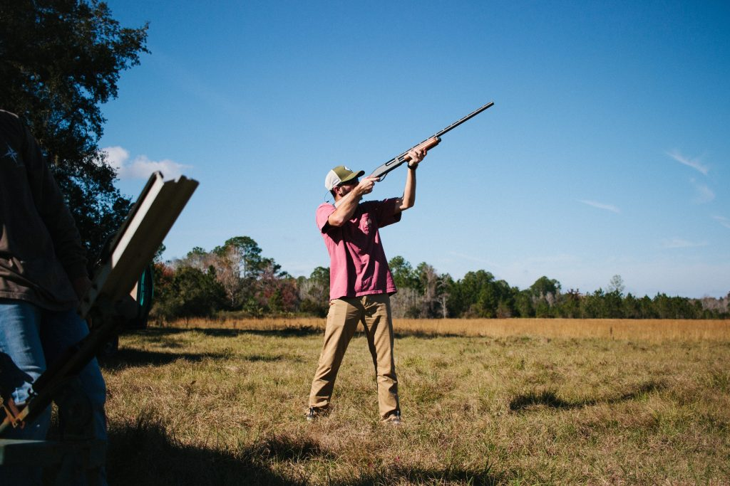 A hunter practicing his marksmanship by shooting clay pigeons.