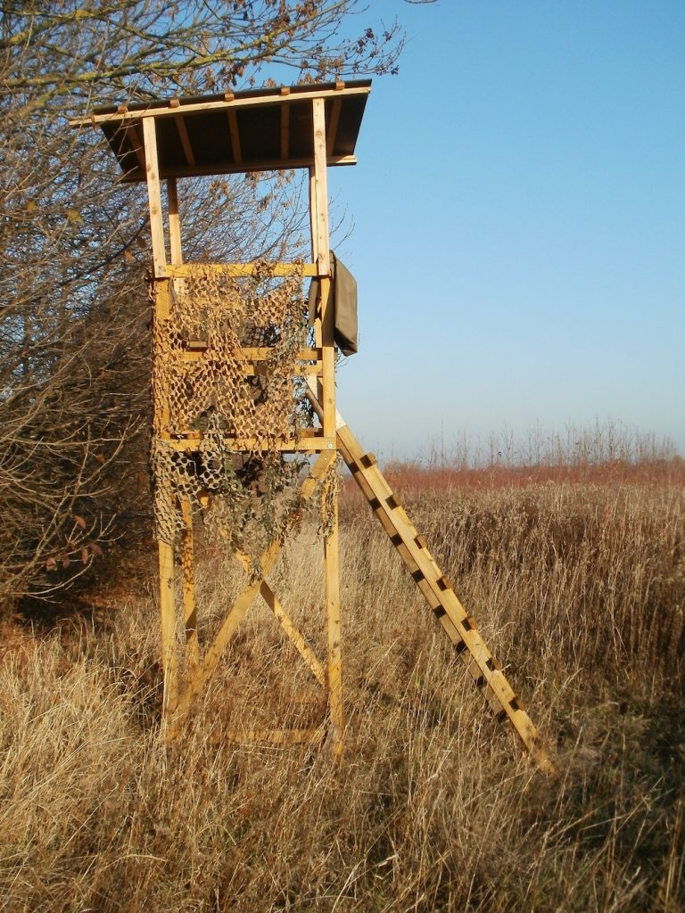 A free-standing deer stand is on the edge of a prairie.