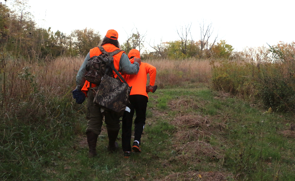 Two hunters in blaze orange hunting gear walking down a path in a prairie. Trees are in the background.
