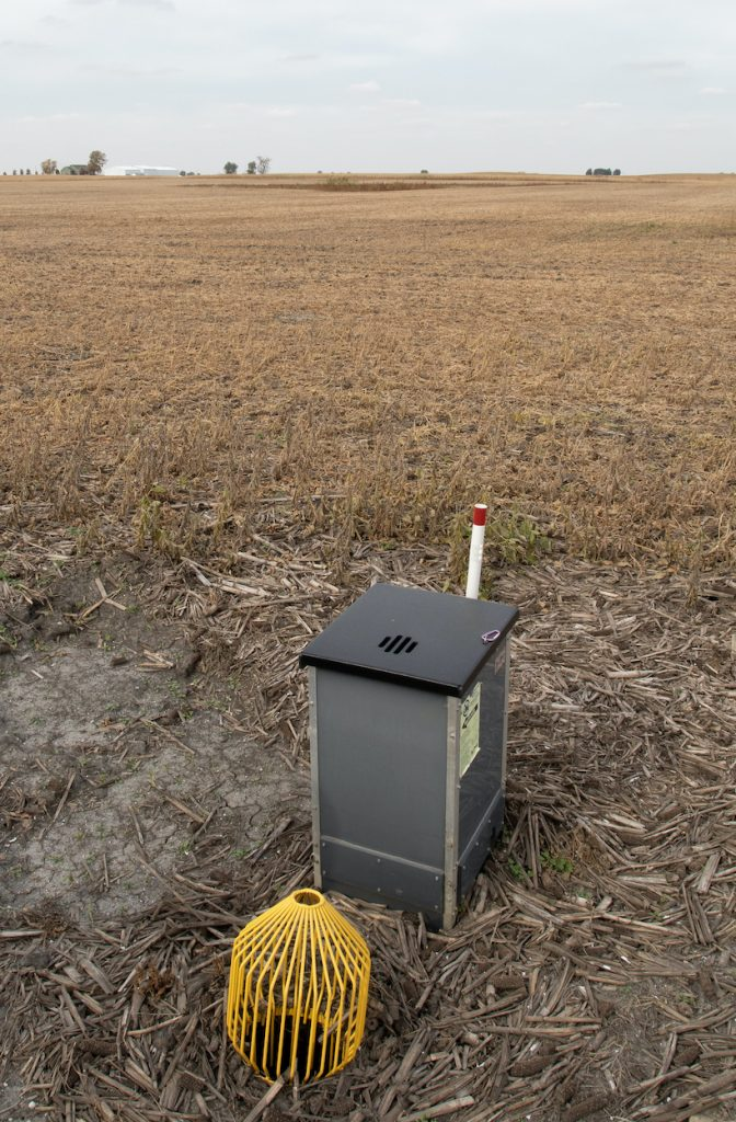 A water control structure in the shape of a metal box with a yellow wire filter over a pipe in a agricultural field during winter.