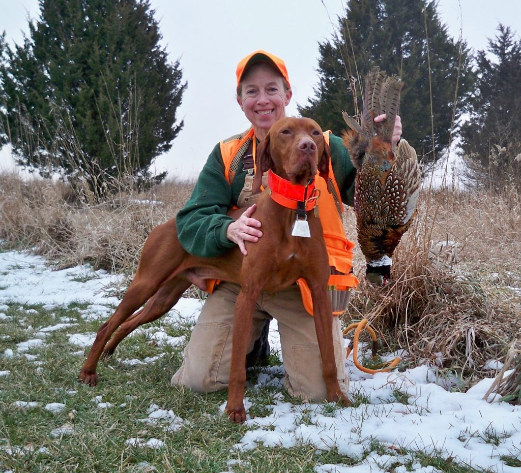 A hunter kneeling next to her hunting dog displays a successful pheasant harvest.