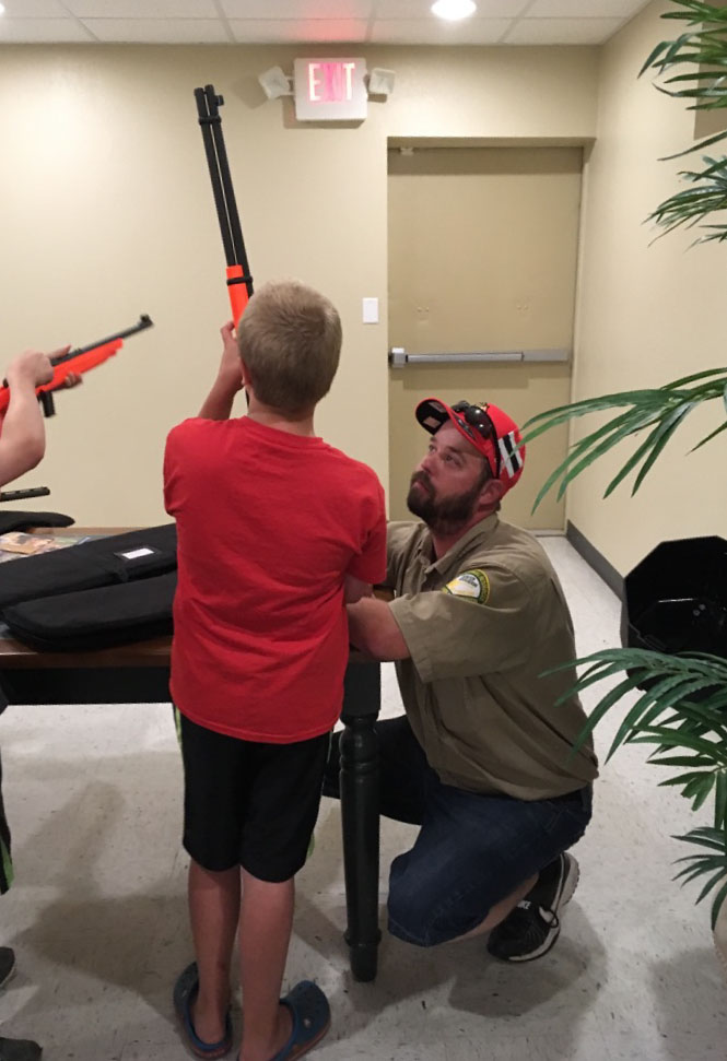 A hunter safety teacher helps a student safely hold a firearm.