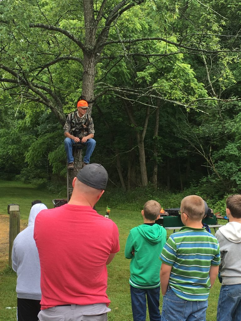 A hunter safety teacher demonstrates a tree stand for deer hunting.