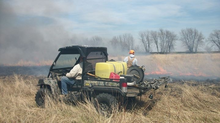 Two men conducting a prescribed burn on a grassland. One man drives an ATV with a water tank. Another man stands outside the vehicle spraying water on the fire line.
