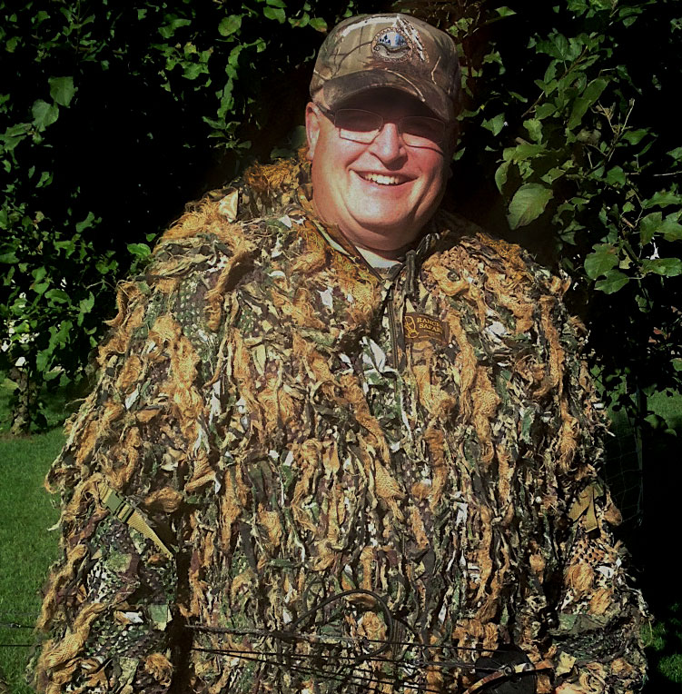 A portrait of a hunter in camouflage gear.