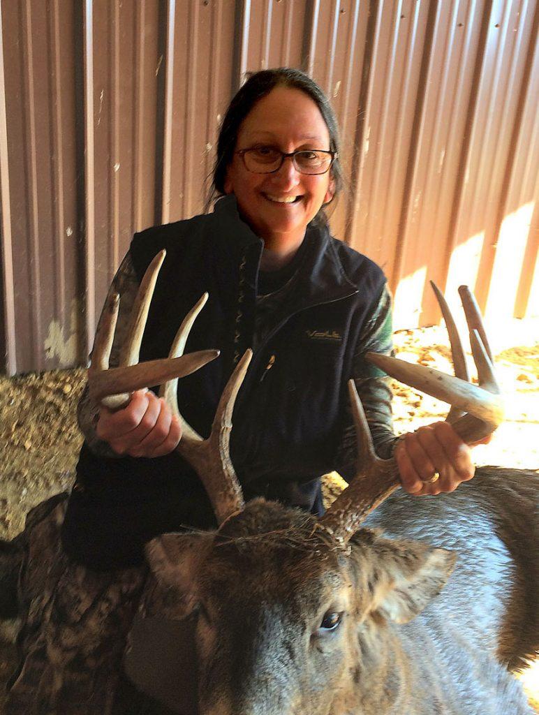 A hunter holds up the antlers of a successful deer harvest. The hunter kneels next to her harvested deer.