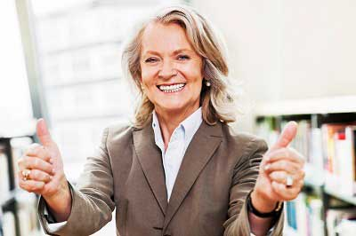 successful woman smiling with thumbs up
