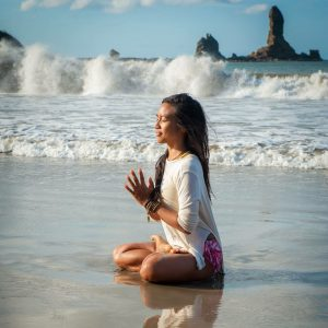 cross legged on beach hands together