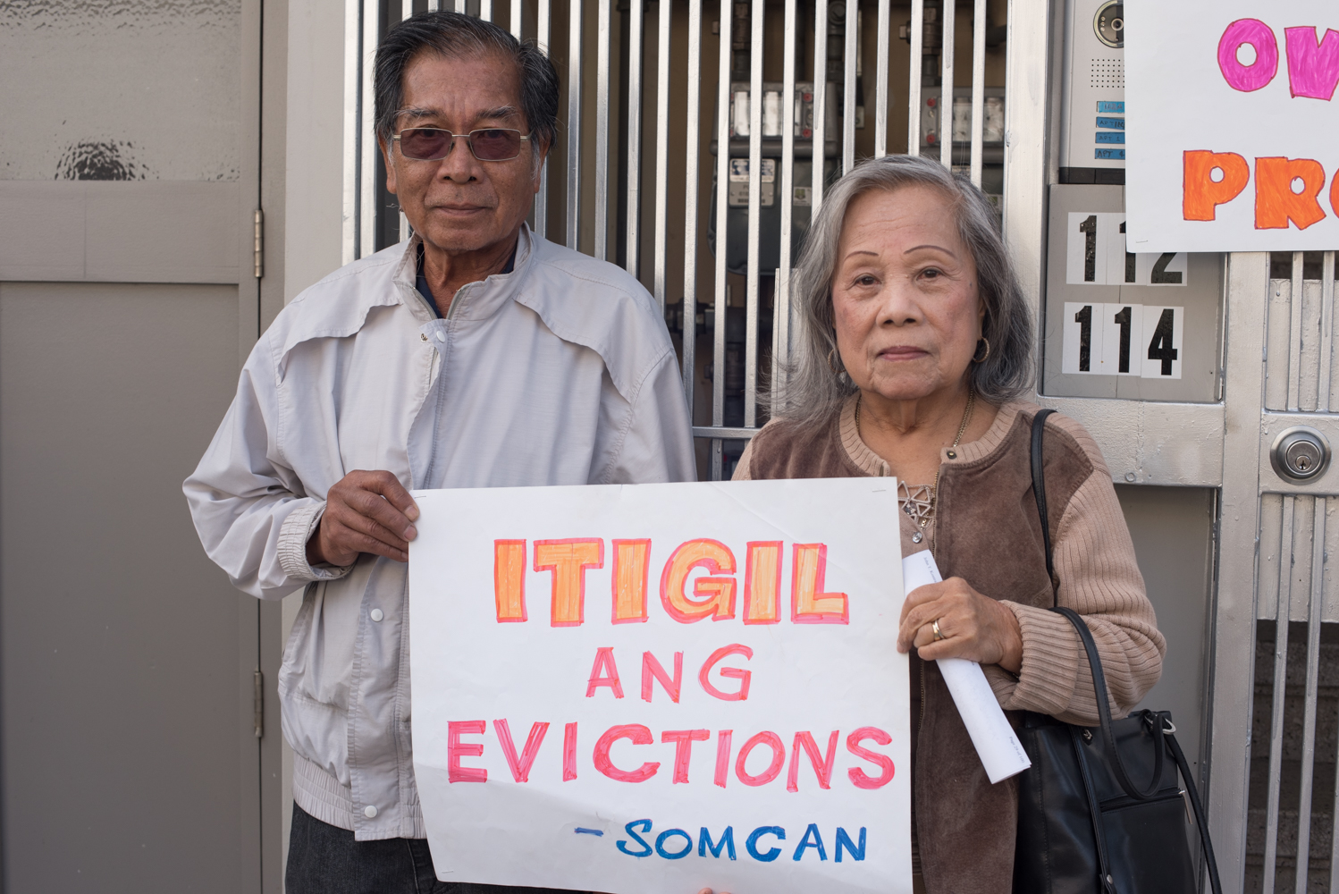 two older people stand holding a sign protesting evictions