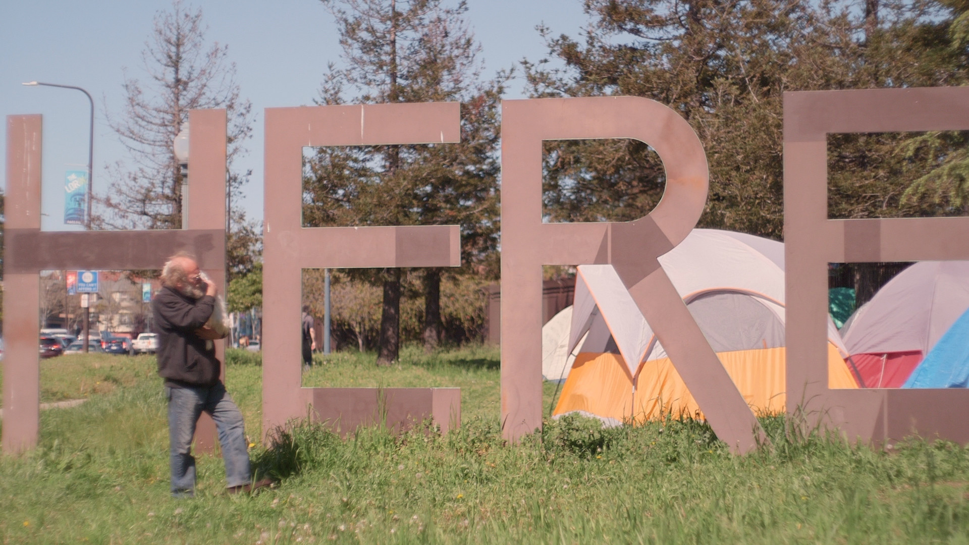 "man standing in grass in front of tall letters ""HERE"""