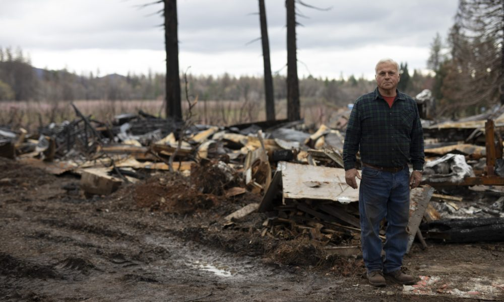 man standing around debris from fire