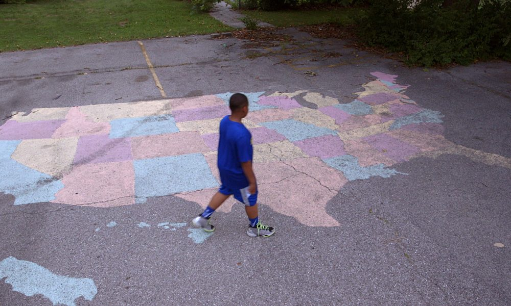 child on pavement with painted U.S. states