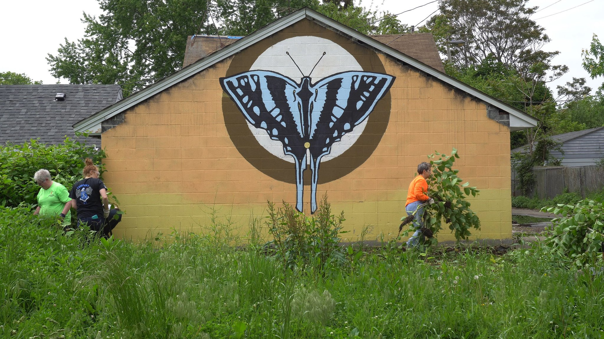 people gardening in front of a building mural with a butterfly