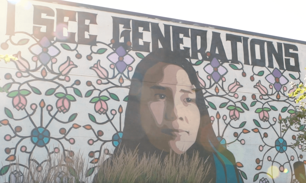 "mural of a lady with flowers and writing that says ""I see generations"""