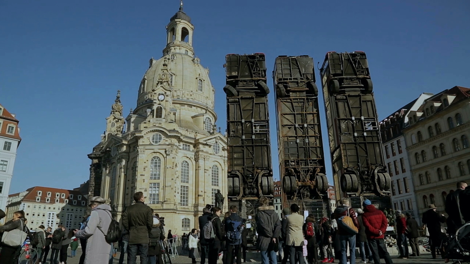 People crowd a plaza in Dresden where three busses are propped up to stand tall in the sky.