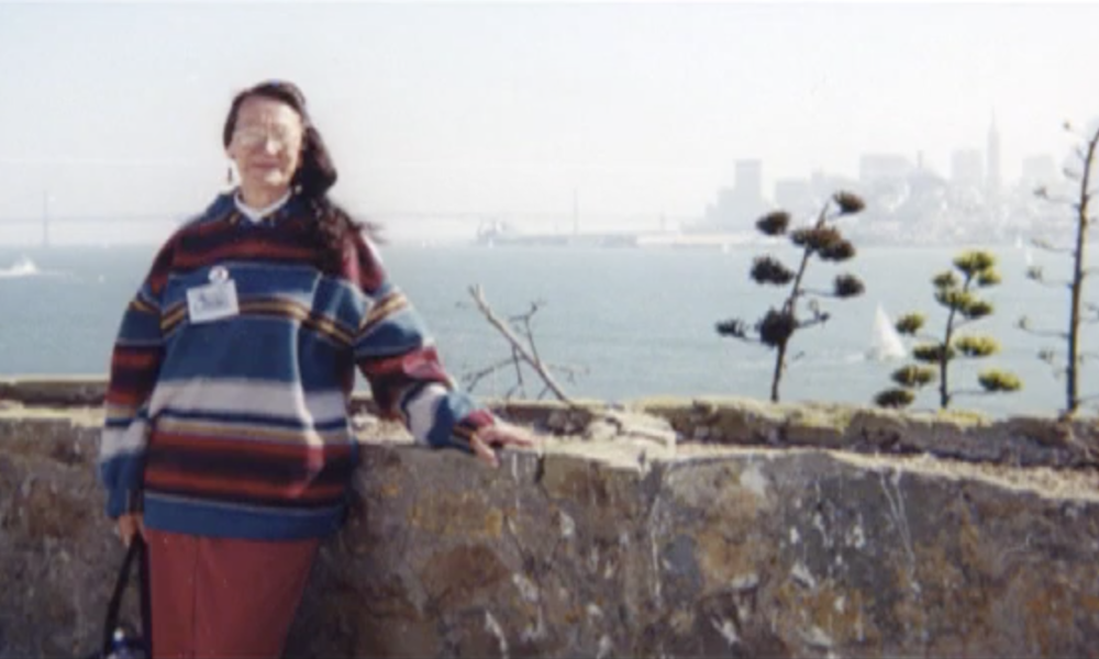 Woman stands in the foreground, the Bay and the San Francisco skyline in the background