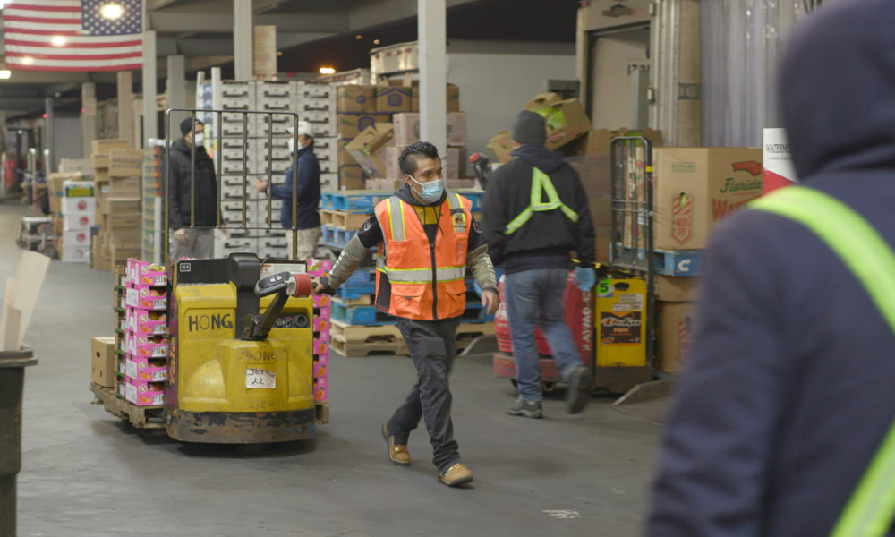 a person wearing a face mask and construction orange vest pulls a piece of equipments in a crowded warehouse