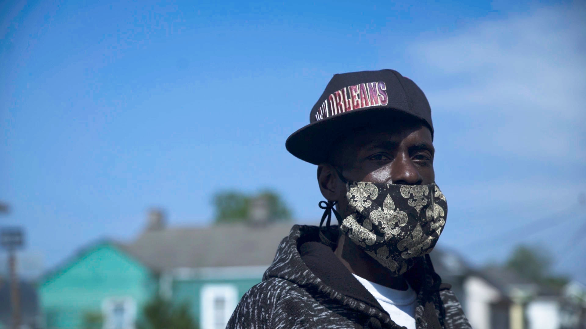 man wearing a hat and face mask looking into the camera with blue skies in the background