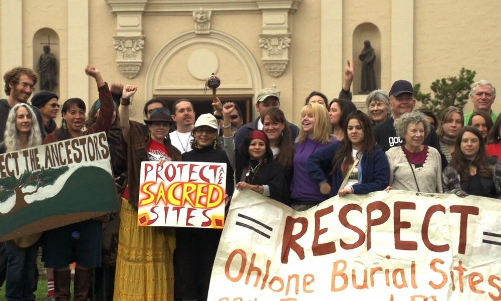 "protestors stand outside of a city building holding signs saying ""Respect Ohlone Burial Sites"""
