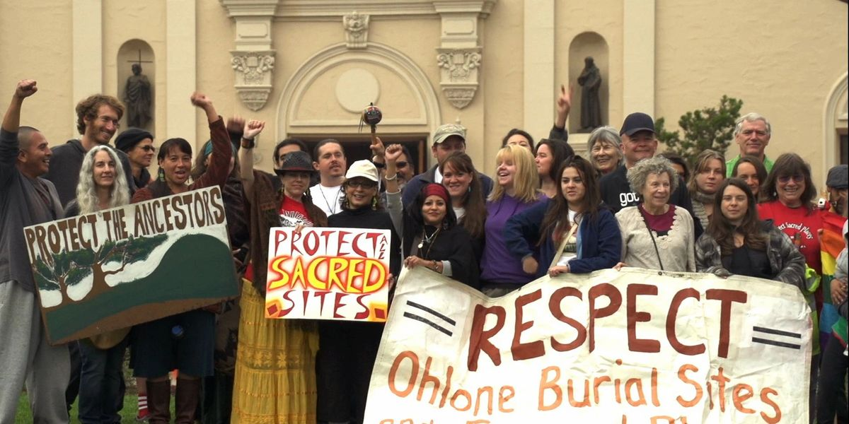"""protestors stand outside of a city building holding signs saying """"Respect Ohlone Burial Sites"""""""
