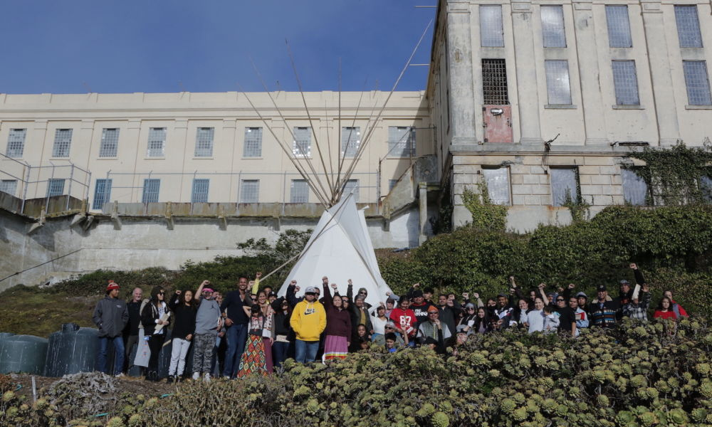 a group of Native folks stand in front of a teepee on Alcatraz Island