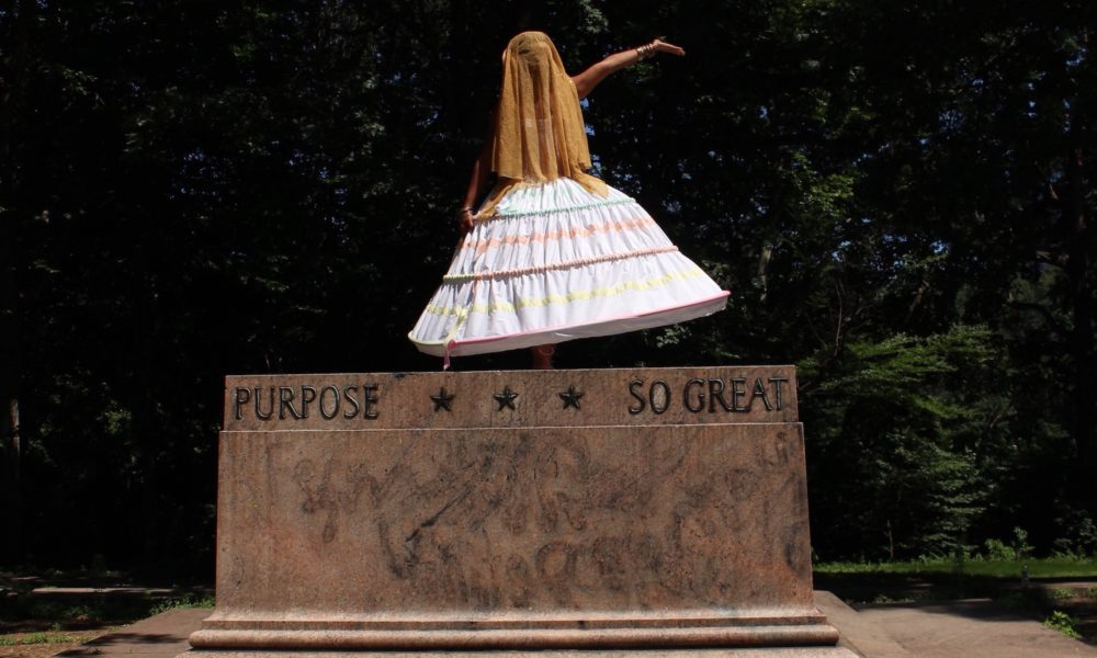 Ada Pinkston, a Black woman, poses on top of a pedestal where a Confederate monument used to stand