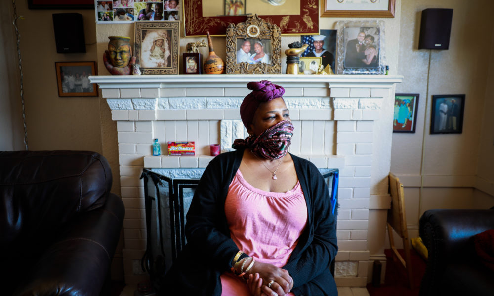 Natalie Henry Berry, a Black woman, sits in her living room wearing a face mask looking out the window.