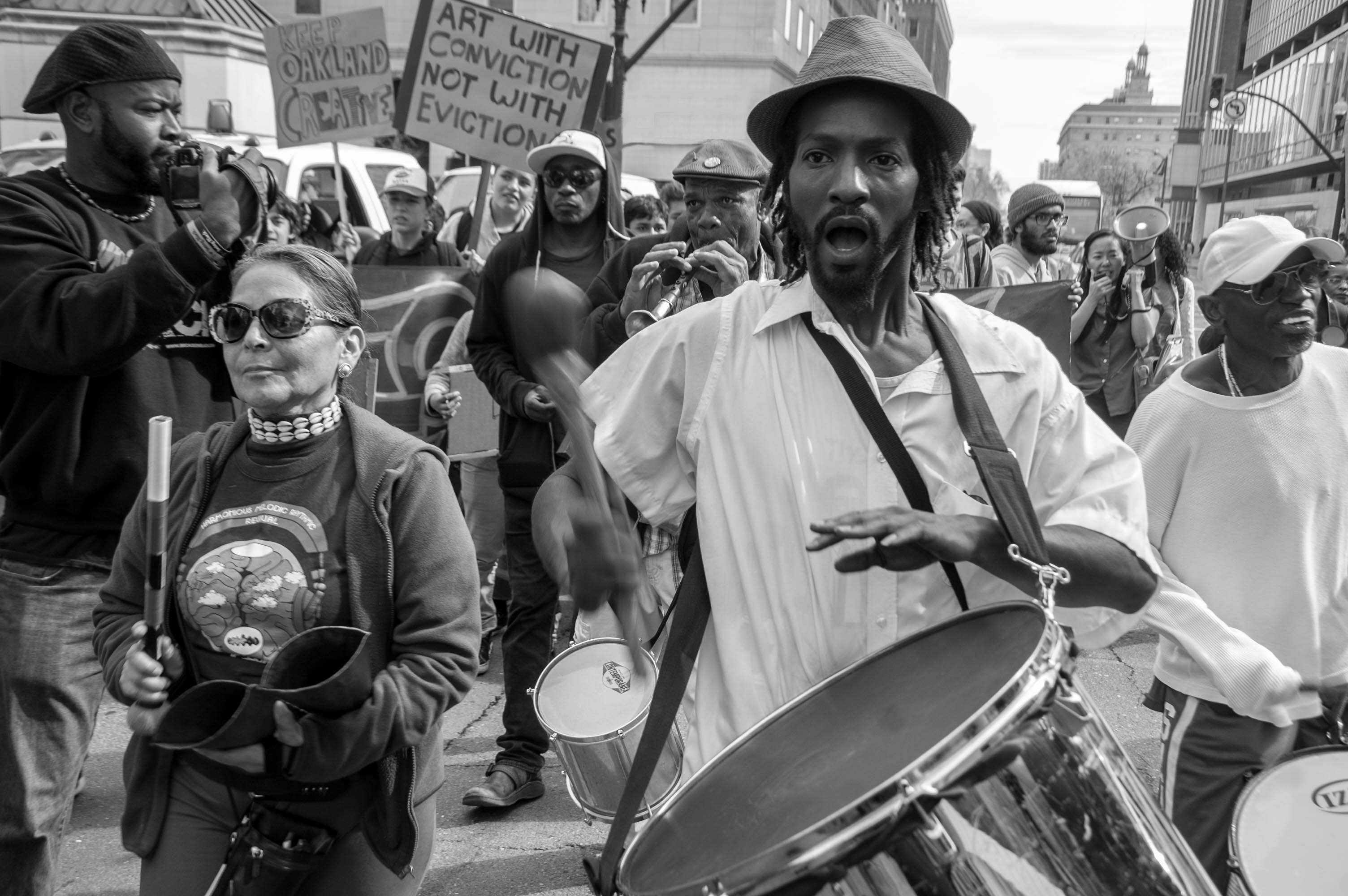 During a protest, a man plays the drums and a woman walks beside him