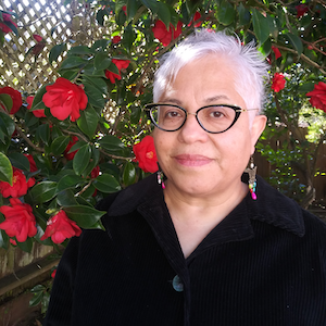 Headshot of Berta Hernandez, a Mexican woman with short gray hair wearing glasses