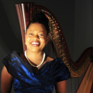 Headshot of Destiny Muhammad, a Black woman in front of a large harp
