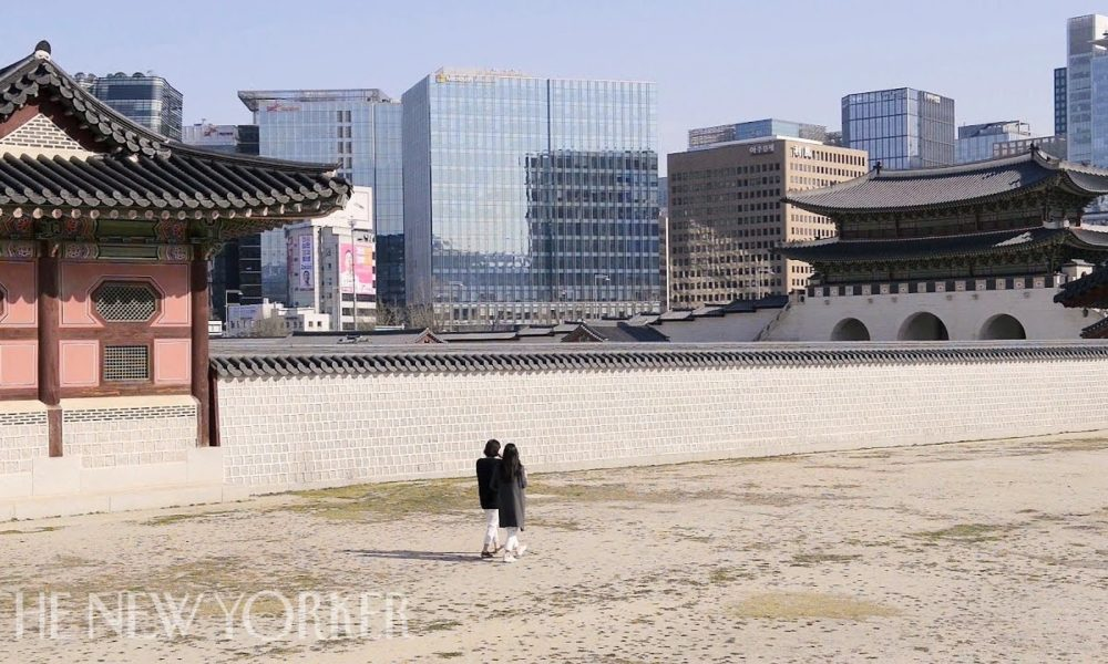 Two people walk in front of an empty Seoul background
