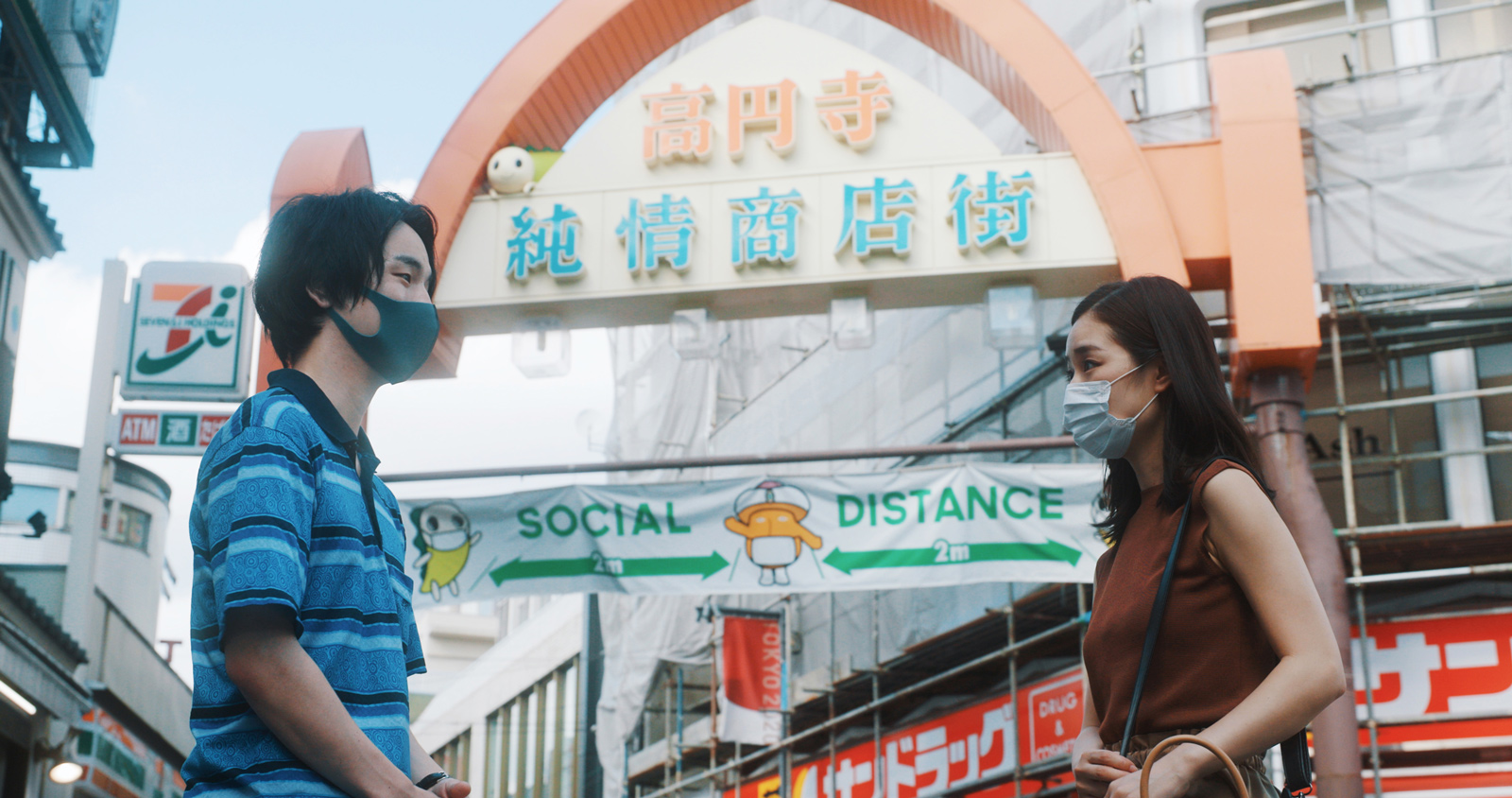 Photo of two people wearing masks with a social distancing sign behind them.